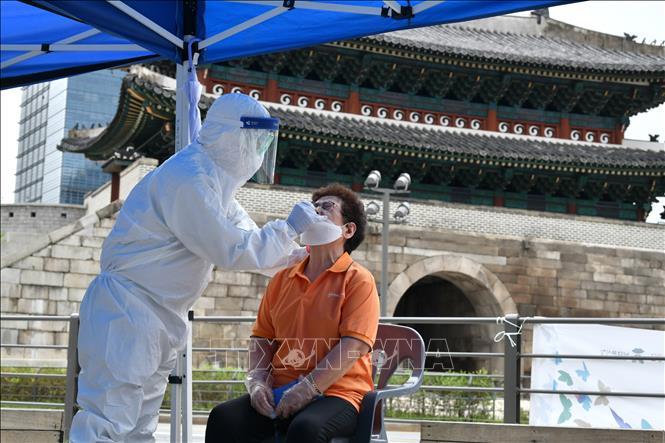 Nhân viên y tế lấy mẫu xét nghiệm COVID-19 cho người dân tại Seoul, Hàn Quốc ngày 10-8. Ảnh: AFP/TTXVN
