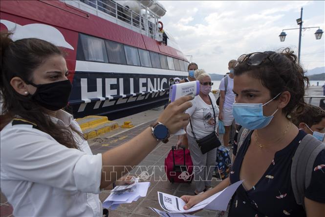 Kiểm tra thân nhiệt du khách nhằm ngăn dịch COVID-19 lây lan tại bến cảng đảo Poros, phía Nam Athens, Hy Lạp ngày 7-8. Ảnh: THX/TTXVN