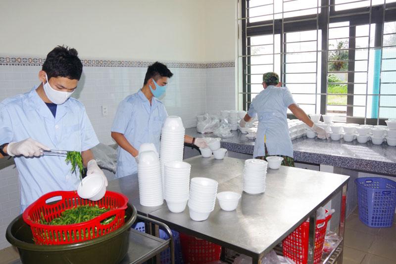 Cán bộ, chiến sĩ phục vụ khu cách ly chia phần cơm cho các công dân. Ảnh: Đặng Thạch