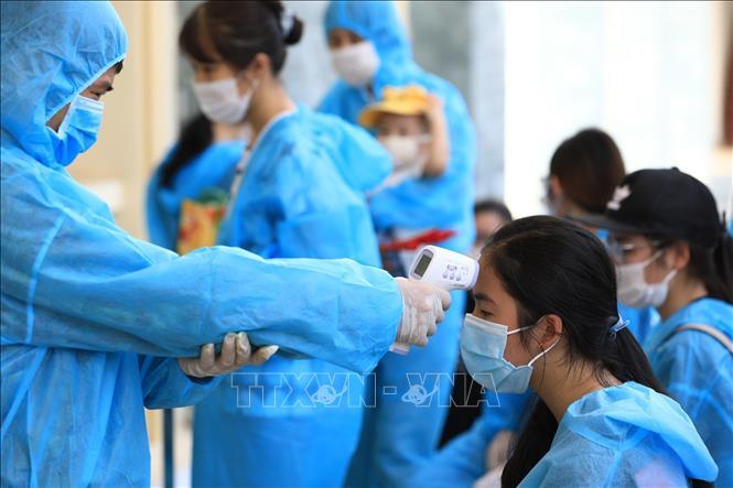 Đo kiểm tra thân nhiệt và làm thủ tục tiếp nhận hành khách về từ Đà Nẵng, tại khu cách ly tập trung Trường quân sự Bộ Tư lệnh Thủ đô. Ảnh minh họa: Thành Đạt/TTXVN