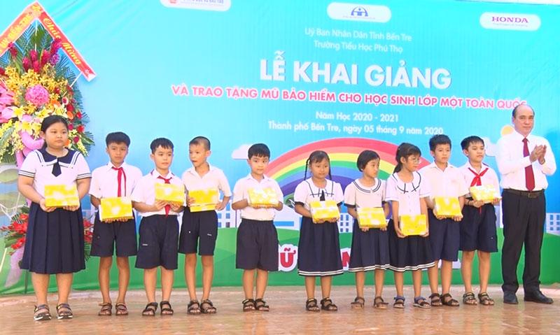 Bí thư Thành ủy Nguyễn Văn Tuấn trao học bổng cho học sinh có hoàn cảnh khó khăn. Ảnh: Hồng Quốc