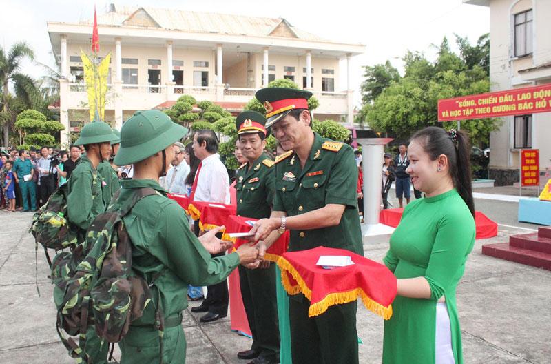 Đại tá Võ Văn Hội - Chỉ huy trưởng Bộ Chỉ huy Quân sự tỉnh tặng quà cho thanh niên huyện Bình Đại lên đường nhập ngũ.  Ảnh: Đ.Thạch