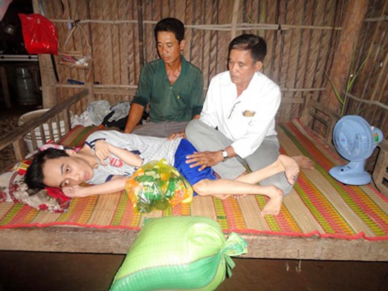 Ông Ba Trí (bìa phải) thăm và tặng quà cho cháu Hà Thanh Liêm, nạn nhân bị ảnh hưởng chất độc da cam ở ấp Đại Thôn, xã Thạnh Phong.