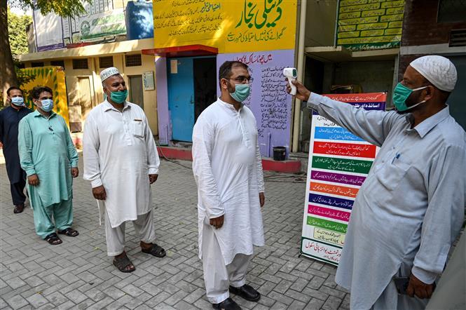 Kiểm tra thân nhiệt phòng lây nhiễm COVID-19 tại Lahore, Pakistan, ngày 12-9-2020. Ảnh: AFP/TTXVN