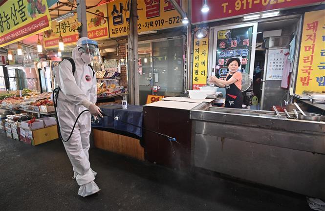 Phun thuốc khử trùng nhằm ngăn chặn sự lây lan của dịch COVID-19 tại một khu chợ ở Seoul, Hàn Quốc ngày 18-8-2020. Ảnh: AFP/TTXVN