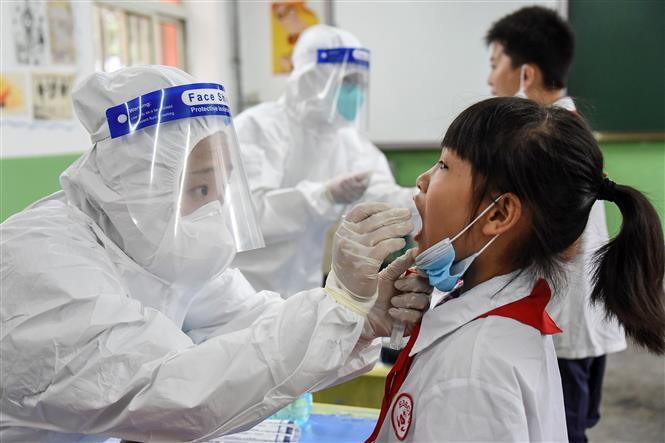 Nhân viên y tế lấy mẫu dịch xét nghiệm COVID-19 cho học sinh tại trường học ở Hàm Đan, tỉnh Hà Bắc, Trung Quốc, ngày 17-8-2020. Ảnh: AFP/ TTXVN